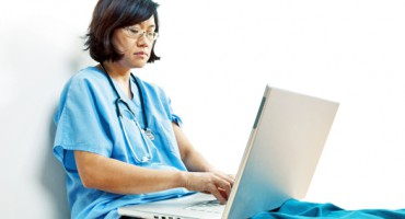 Woman Doctor or Nurse at Laptop Computer, Seated