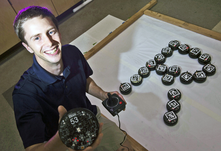 Aaron Becker with a small robot swarm. (Credit: Jeff Fitlow/Rice University)
