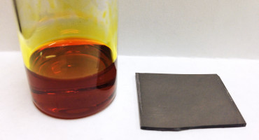 On the left, bulk antimony triselenide (Sb2Se3) dissolved in the new solvent mixture. On the right, a thin film of antimony triselenide derived from that solution using low-cost and low-energy input processing methods. This technique could make it less expensive to process semiconductors for transistors, solar cells, LEDs, and more. (Credit: Jannise Buckley)