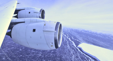 During a flight over the Pine Island Glacier ice shelf, the DC-8 banks over the Amundsen Sea and the clean edge of the ice shelf front. The shelf drops about 200 feet from its surface to sea level. This image was taken on Oct. 26, 2011. (Credit: Jefferson Beck/NASA)