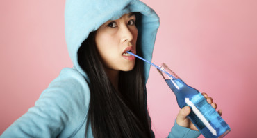 woman drinks a blue soda