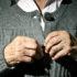an elderly person buttons sweater