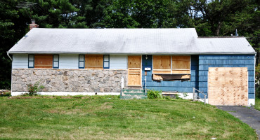 foreclosed home with boards over windows