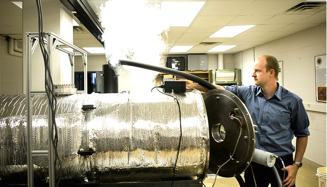 Erik Fischer sets up a Mars atmospheric chamber by running liquid nitrogen to cool it down. (Credit: Joseph Xu)