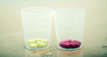 two cups with yellow and pink pills