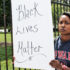 "woman's sign says ""black lives matter"""
