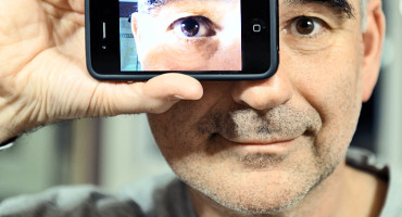 man holds iPhone photo of eye over his eye