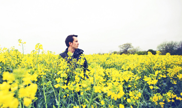 man in field of yellow flowers