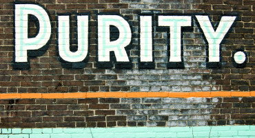 word purity painted on brick wall