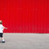young boy walks in front of a red wall