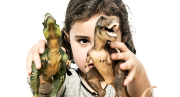shy child plays with dinosaurs
