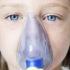girl with asthma uses an inhaler