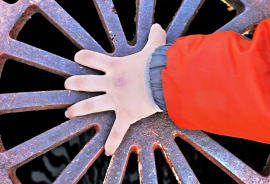 child's hand on a metal grate
