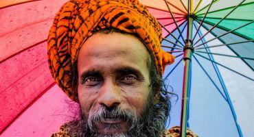 man under a rainbow umbrella