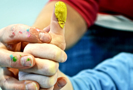 preschool teacher helps child fingerpaint