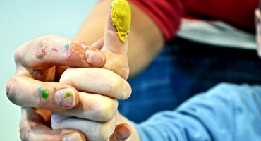 preschool teacher helps child fingerpaint