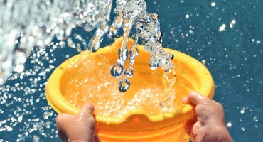 child throws water from a yellow bucket