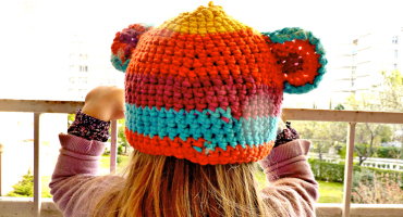 little girl wearing a colorful cap