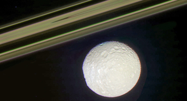 moon Mimas seen near Saturn's rings