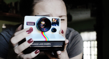 a woman takes a picture with a polaroid camera