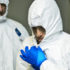 man puts on an Ebola protective suit