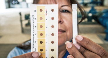 woman holds arsenic test strip