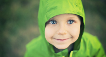 little boy in a green jacket