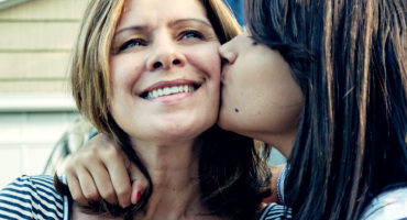 daughter kisses mom on the cheek