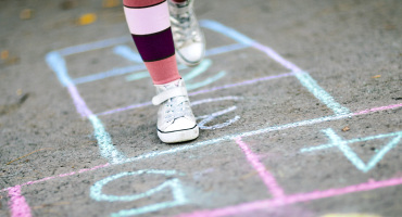kid plays hopscotch