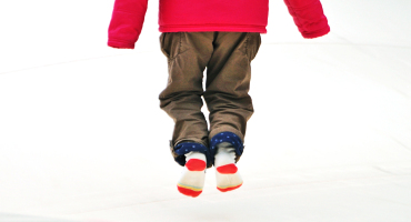 child in parka and socks jumps