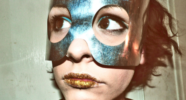 woman wears mask and gold glitter