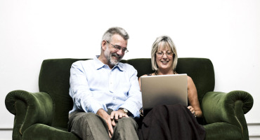 mid-life couple on couch with laptop