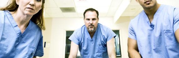 nurses push gurney in hospital