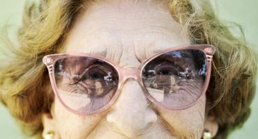 elderly woman wears pink sunglasses