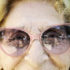 elderly woman wears pink sunglasses