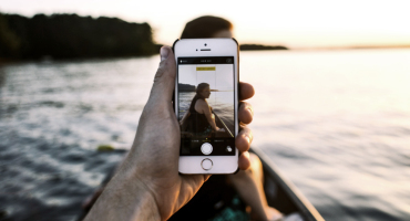man uses iphone on canoe with woman