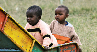 two Kenyan children play on slide