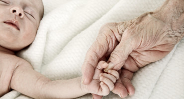 newborn baby holds grandparent's hand