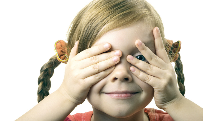 little girl peeks through her fingers