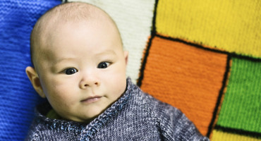 baby in sweater on knit blanket