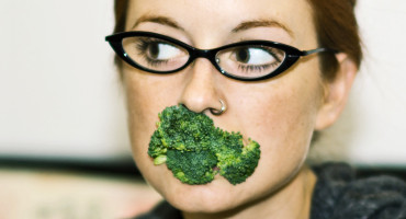 woman holds broccoli in mouth