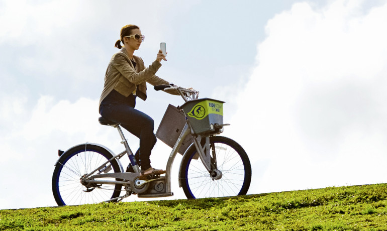 woman looks at iphone while riding bike