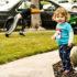 kid mows lawn near little sister