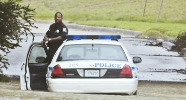 police officer waits for help during a flood
