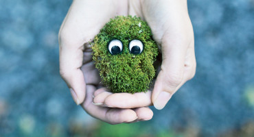 woman holds sad moss Earth with eyes