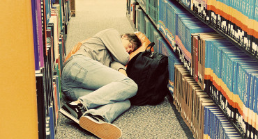 college student sleeps in the library stacks