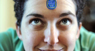 smiling woman with a sticker on her forehead