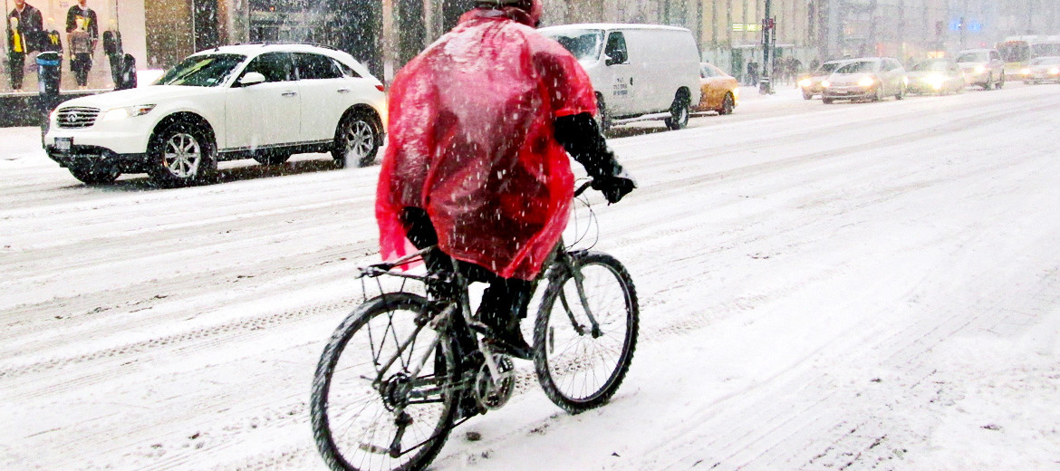 man rides bike through snow in poncho