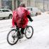 man rides bike through snow in poncho