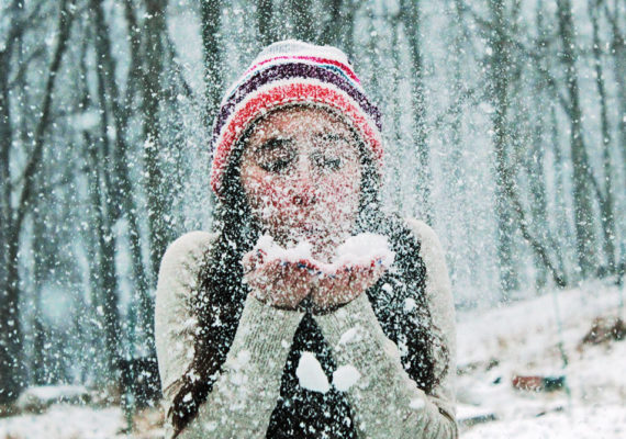 woman blowing snow into the air